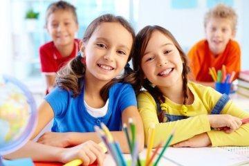Four young children smiling in a classroom l pediatric dentist wylie tx