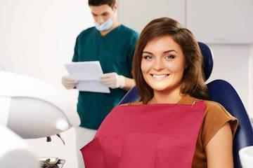 woman smiling in dental chair after root canal with dentist standing behind her l root canals wylie tx