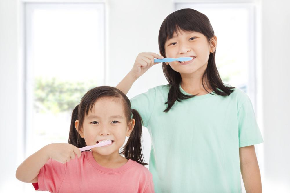 two young girls brushing teeth l dentist in wylie tx