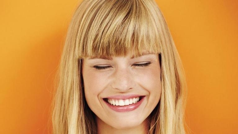 woman smiling with orange background